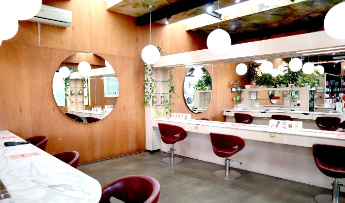 Hair stylist seating in a well-lit space with a round mirror on a wall