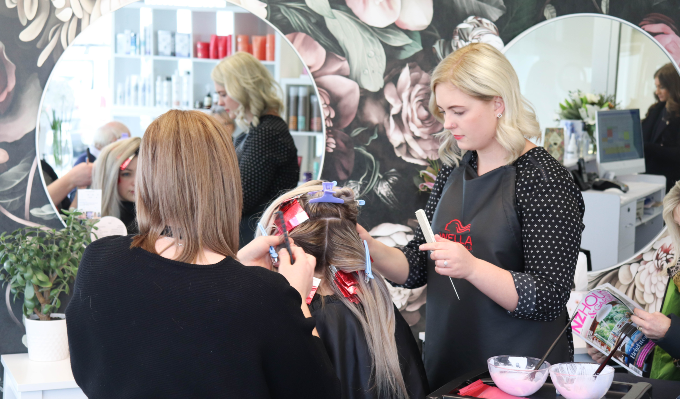 Two hair stylists dividing client's hair into sections at a hair salon