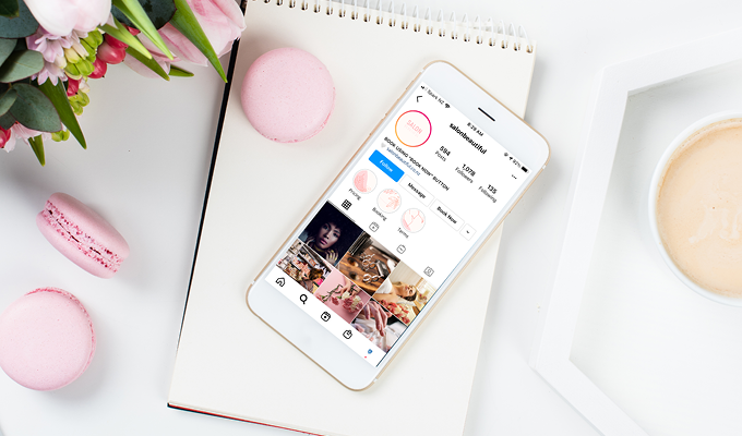 Instagram opened on a smartphone lying on top of a notepad next to a pink macaroon and pink tulips